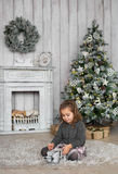 Pretty little girl sits on a floor and plays with wooden toy near a fireplace in Christmas at home Royalty Free Stock Image