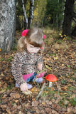 Pretty little girl sits next red toadstool Royalty Free Stock Photography