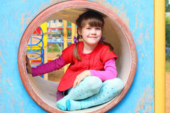 Pretty little girl sits in pipe on playground Stock Images