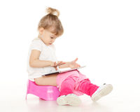 Pretty little girl sits on potty. Royalty Free Stock Images