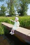 Pretty little girl sits, shows thumb on bridge Stock Photography
