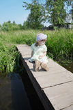 Pretty little girl sits on small bridge in village Stock Photo
