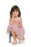 Pretty the little girl sits on a stool. It is isolated on a white background Royalty Free Stock Images