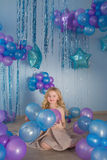 Pretty little girl sits in a studio with balloons. Pretty little girl sits in a studio with a lot of color balloons Royalty Free Stock Photo