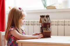 Pretty little girl sits at table with small wooden toy house Royalty Free Stock Photo
