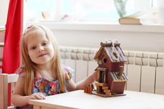 Pretty little girl sits at table with small wooden toy house Royalty Free Stock Images