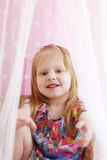 Pretty little girl sits among transparent curtains Royalty Free Stock Image