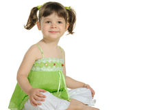 Pretty the little girl sits on the white Royalty Free Stock Photos