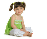 Pretty the little girl sits on the white Royalty Free Stock Image