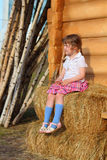 Pretty little girl sits on yellow hay near wall of wooden house Royalty Free Stock Image