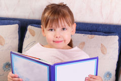 Pretty little girl sitting with book Stock Image
