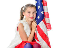 A pretty little girl sitting on a box with a american flag Stock Images