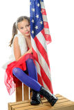 A pretty little girl sitting on a box with a american flag Stock Photography