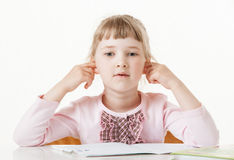 Pretty little girl sitting with closed ears at school desk Royalty Free Stock Image