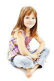 Pretty little girl sitting on the floor in jeans Stock Images