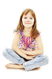 Pretty little girl sitting on the floor in jeans Stock Image