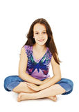 Pretty little girl sitting on the floor in jeans Stock Photo