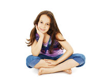 Pretty little girl sitting on the floor in jeans Royalty Free Stock Photography
