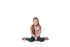 Pretty little girl sitting on the floor in jeans Royalty Free Stock Image
