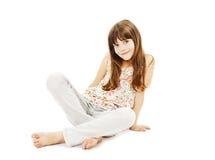 Pretty little girl sitting on the floor in jeans. Closeup image of a pretty little girl sitting on the floor in jeans. on white background stock photos