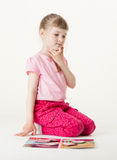 Pretty little girl sitting on the floor and thinking about game Stock Image