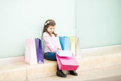 Pretty little girl sitting with shopping bags outside mall. Pretty little latin girl sitting outdoors of a mall with lots of shopping bags Royalty Free Stock Images