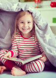 Pretty little girl sitting under blanket Royalty Free Stock Photo
