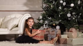 Pretty little girl is sitting under Christmas tree in evening of celebration day. Child girl is well-dressed and happy, is sitting on a carpet in a hall near a stock video footage