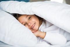 Pretty little girl in sleepwear lying under blanket in the bed at home. Pretty little girl in sleepwear lying under blanket Stock Photo