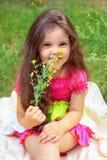 Pretty little girl smelling flowers. Pretty little girl smelling yellow flowers Royalty Free Stock Image