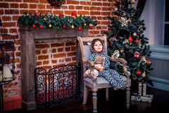 Pretty little girl smiling with teddy bear near the Christmas tree sitting in vintage chair. Happy New Year. Royalty Free Stock Photography