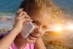 A pretty little girl speaks by smartphone, smiling and squinting in sunshine on sea background. Sunset 1 Royalty Free Stock Images