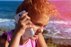 A pretty little girl speaks by smartphone, squinting in sunshine on sea background. Sunset 4 Stock Photos