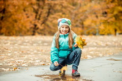 Pretty little girl squatting with leaves in hand Stock Photo