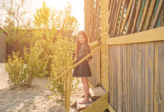Pretty little girl on stairs of wooden house Stock Images