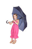 Pretty little girl standing. Holding a blue umbrella Royalty Free Stock Images