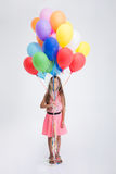 Pretty little girl standing with balloons Royalty Free Stock Image