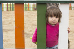 Pretty little girl standing behind fence Stock Photo