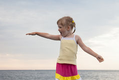 Pretty little girl standing on the embankment Stock Photography