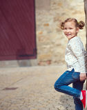 Pretty little girl standing near the wall Stock Image