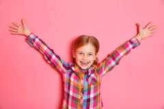 Pretty little girl standing on pink background with raised hands up. Royalty Free Stock Photography