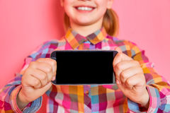 Pretty little girl standing and showing a screen of phone on pink background. Copy space. Royalty Free Stock Images