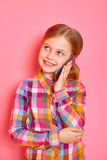 Pretty little girl standing and talking a phone on pink background Royalty Free Stock Image
