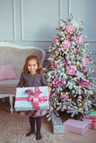 Pretty little girl stands and holds a gift box at hands near Christmas tree Stock Image