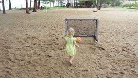 Pretty little girl stands near mini football gates and claps stock video