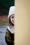 Pretty little girl in the street. Be hiding before a yellow wall Stock Image