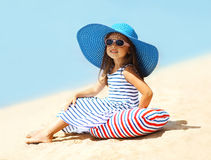 Pretty little girl in a striped dress. And hat relaxing on the beach near sea, summer, vacation, travel - concept Stock Photos