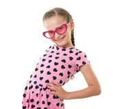 Pretty little girl studio portrait, dressed in pink with heart shapes, white background Royalty Free Stock Image