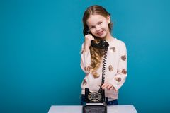 Pretty, little girl in sweater with brunet hair have a phone talk. Isolated on blue, attractive caucasian brunette child with long hair, in beige coat and blue Royalty Free Stock Images