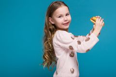 Pretty, little girl in sweater with brunet hair hold a burger. Isolated on blue, attractive caucasian brunette child with long hair, in beige coat and blue jeans Stock Images